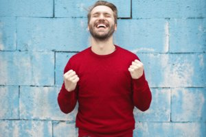 happy man in red sweater with a big smile and pumping fists against blue wall